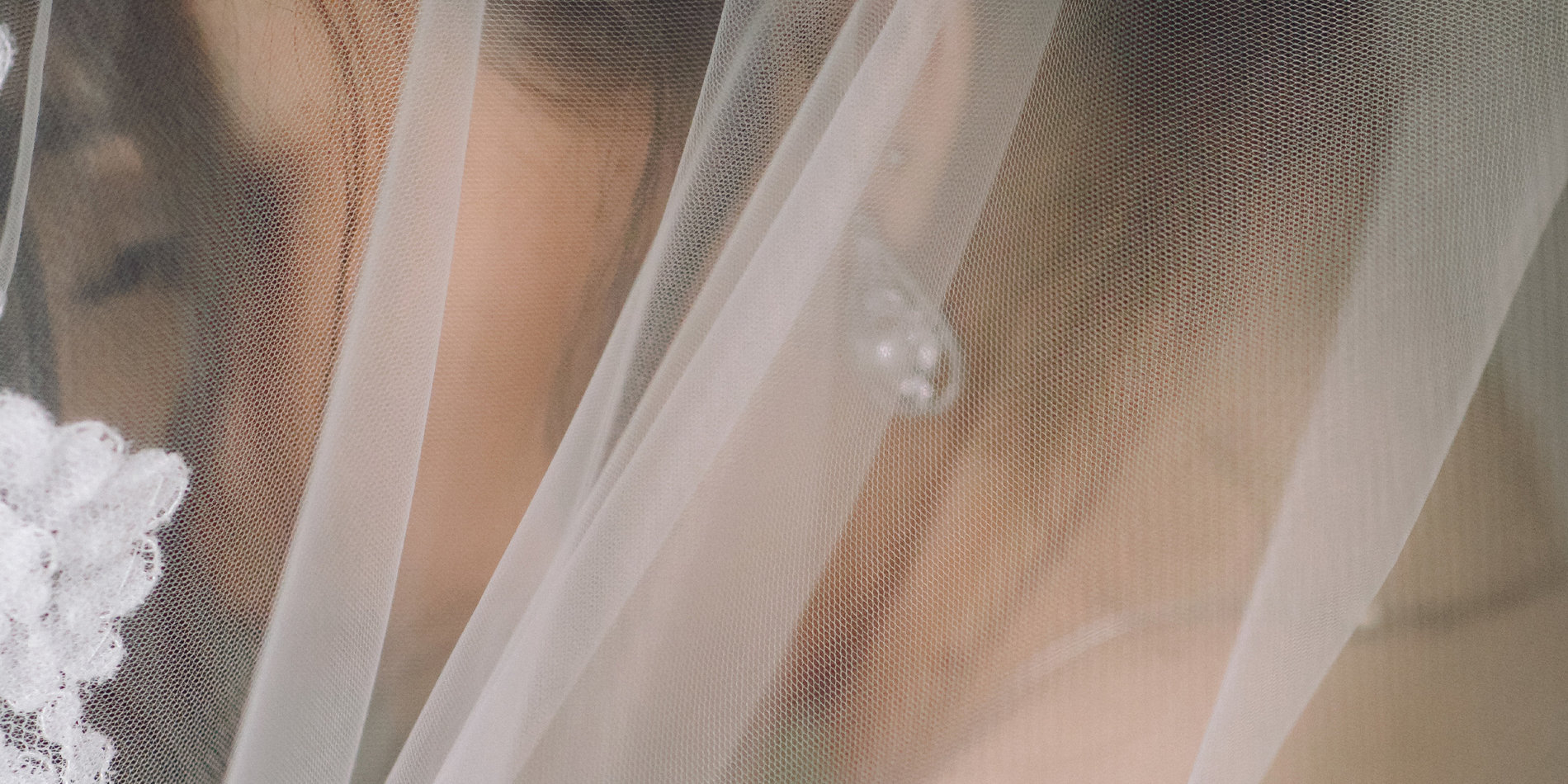 Banner image featuring a macro shot of a bride underneath her veil, via Freepik Licensed through Student Affairs.
